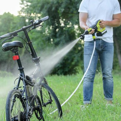 A man cleaning a bike with pressure washer